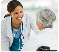 Doctor leans down to smile at elderly patient turned towards her