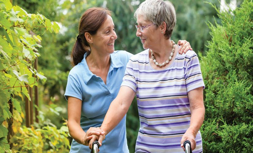 Woman puts arm around elderly woman's shoulder during a walk outside.